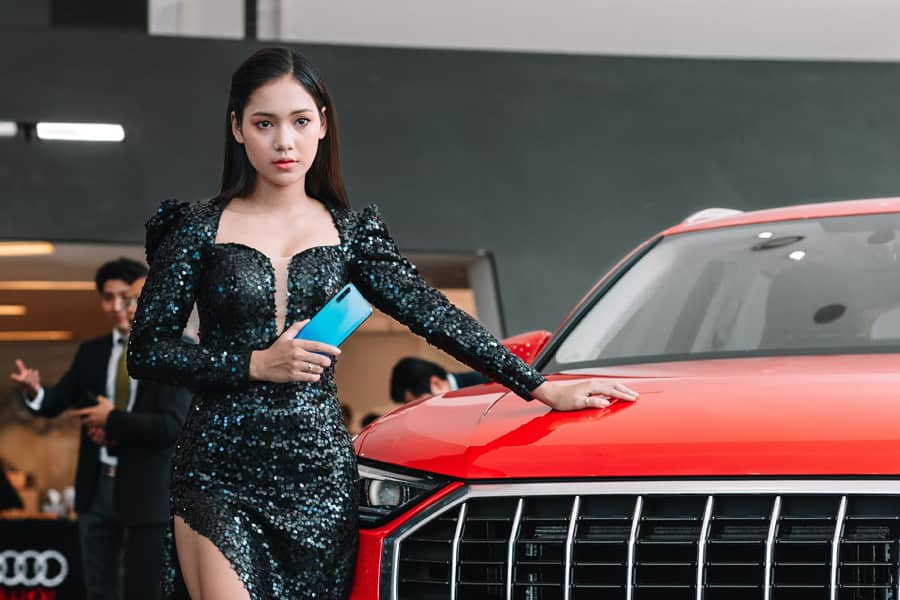 woman next to a red car